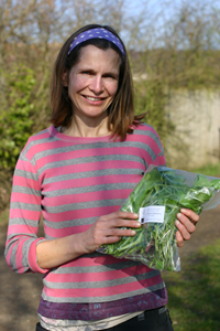 Picture of Sarah from Ripple Farm with a bag of their salad leaves